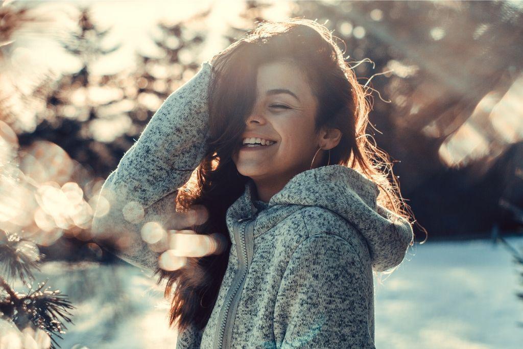 Nainen hymyilee silmät kiinni talviauringossa
