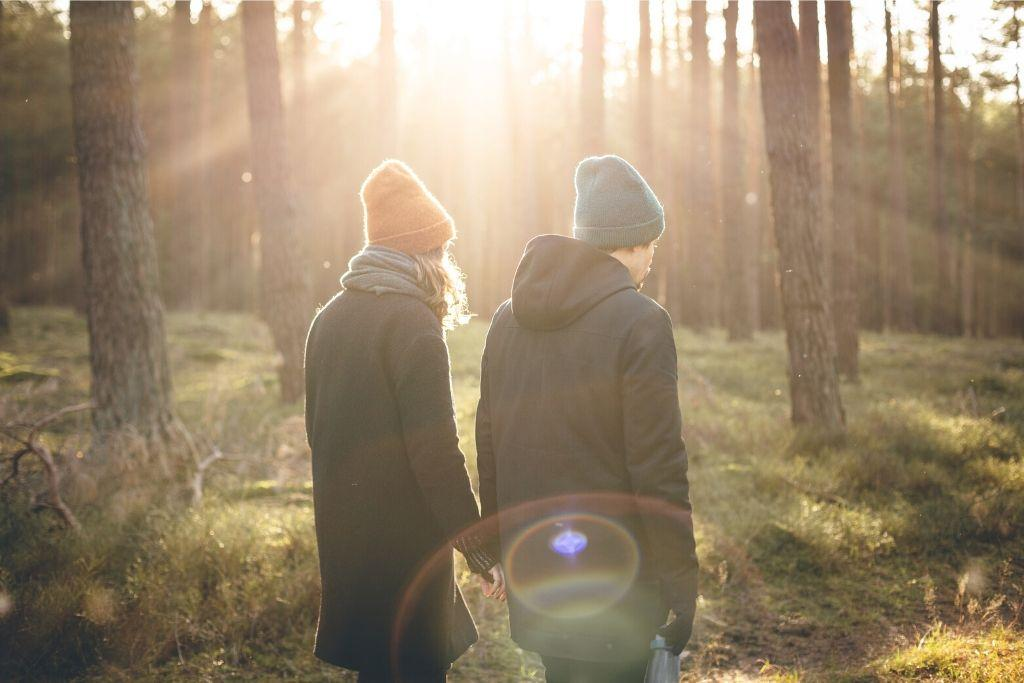 Pariskunta kävelee aurinkoisessa metsässä