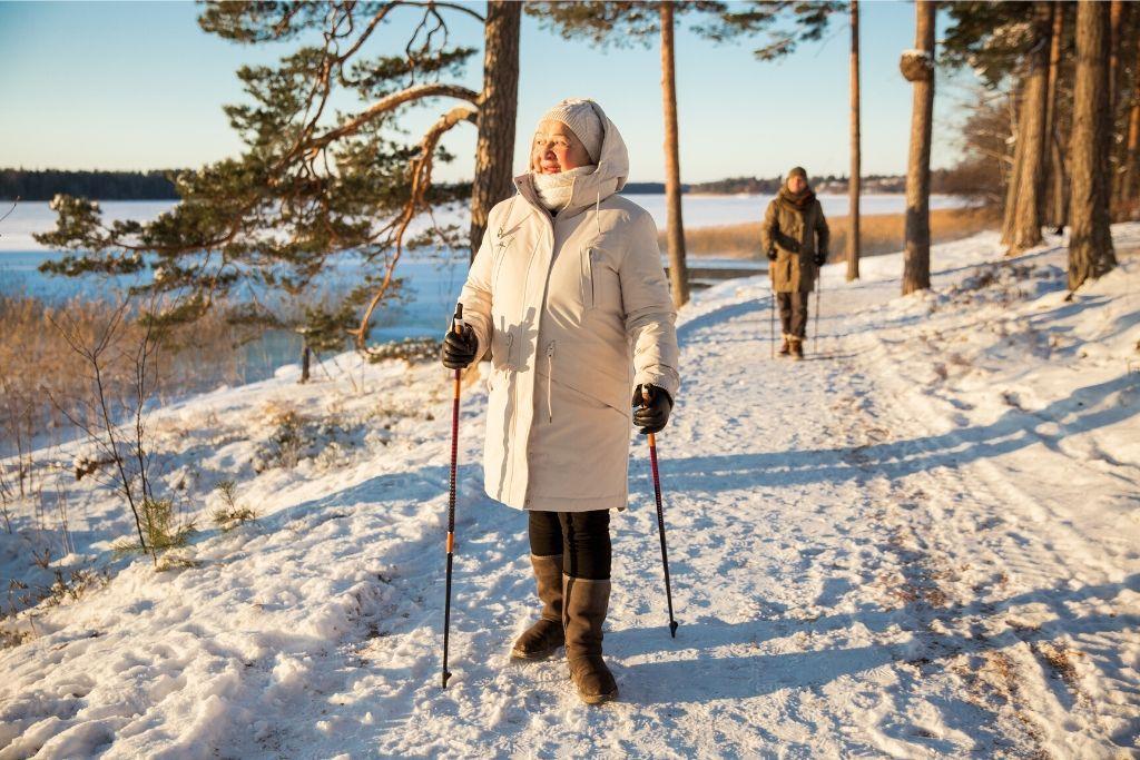 Iäkäs nainen ulkoilee aurinkoisena talvipäivänä.