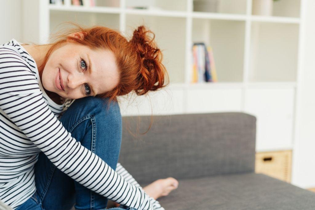 nainen nojaa päätä polveen sohvalla