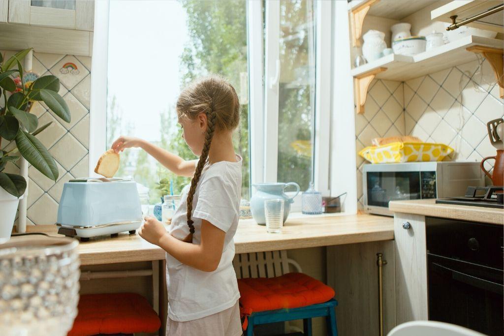 Tyttö paahtaa leipää