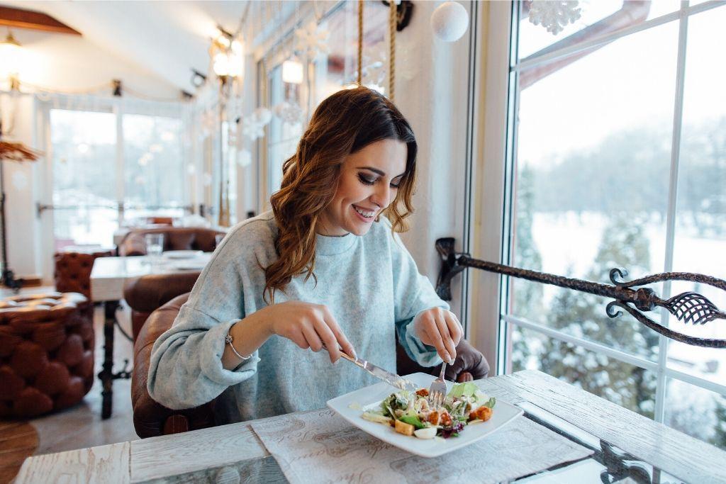 nainen ruokailee lasiterassilla