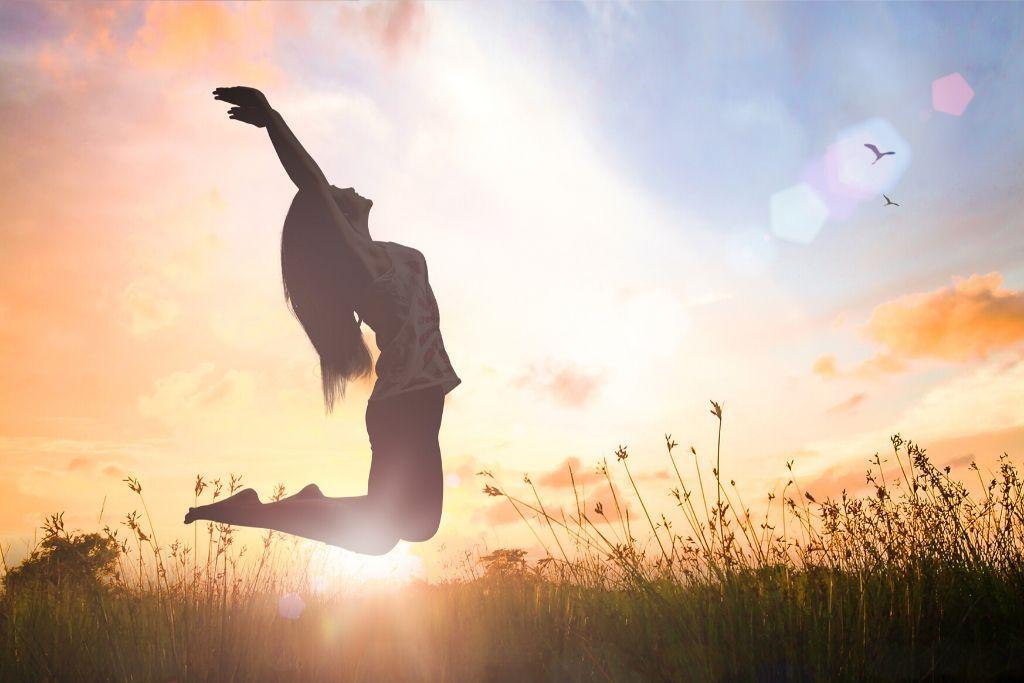 Nainen hyppää pellolla.