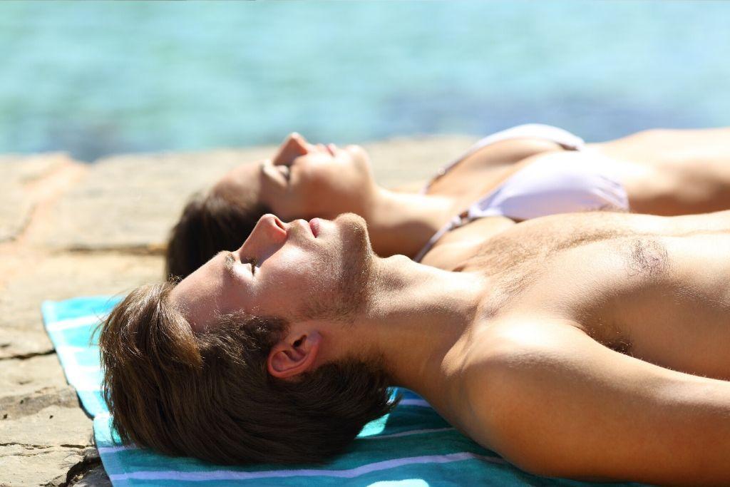 D-vitamiinia tankkaavat nainen ja mies rannalla.