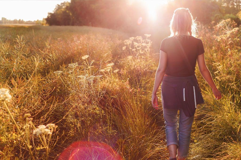 Nainen kävelee pellolla.