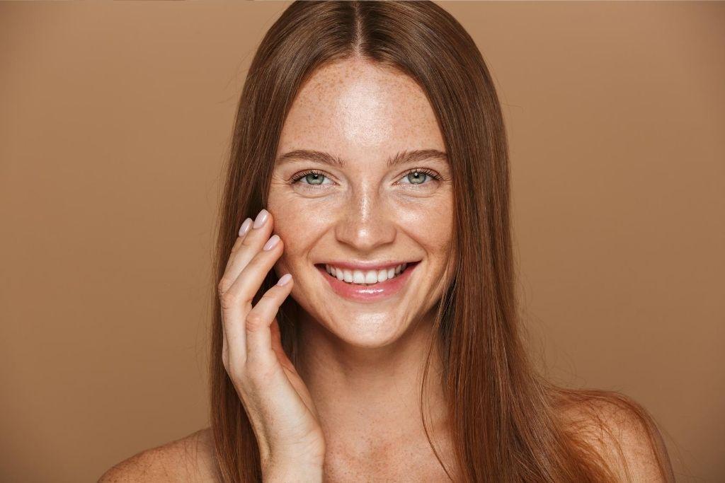 Kaunis ruskeatukkainen nainen hymyilee.