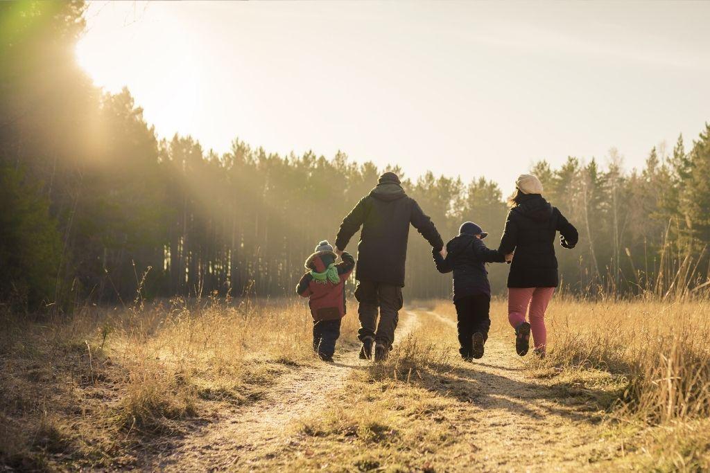 Perhe kävelee syksyisellä pellolla.