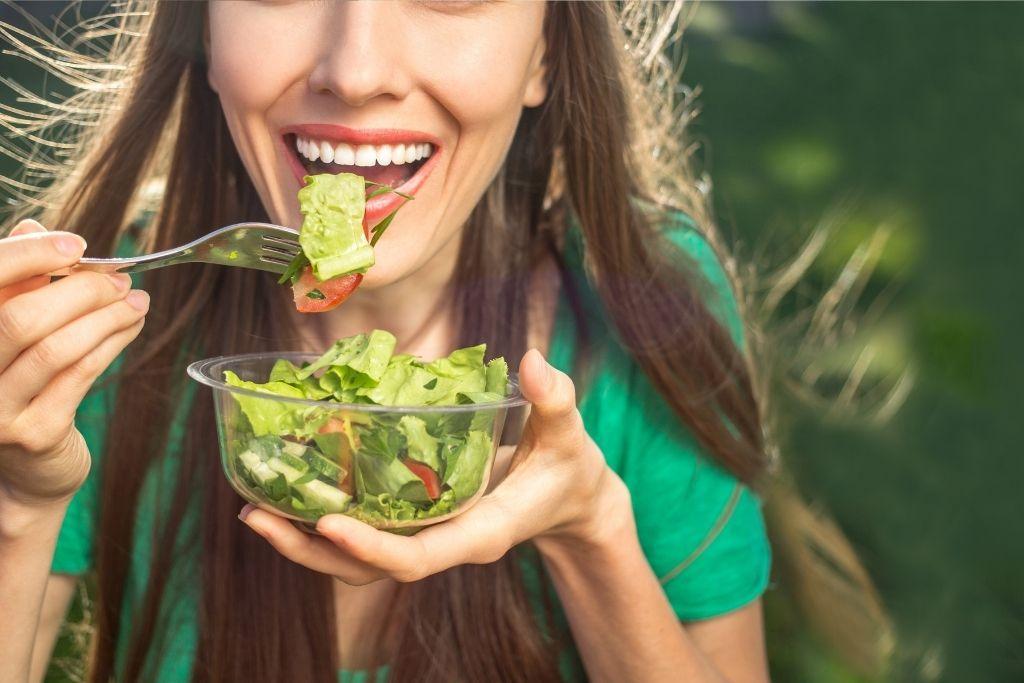 Nainen syö salaattia.