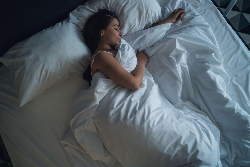 Nainen nukkuu sängyssä.