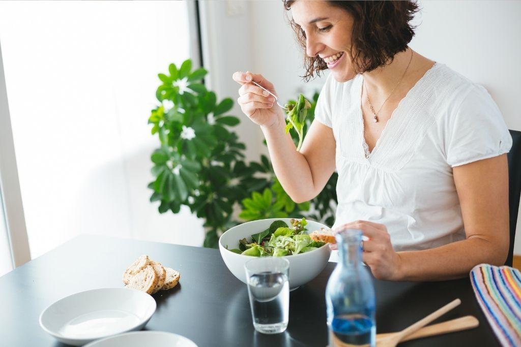 Raskaana oleva nainen syö salaattia