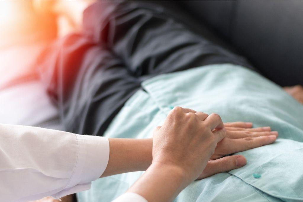 Lääkäri tutkii potilaan paksusuolen toimintaa vatsan päältä.