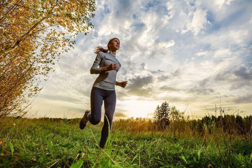 Nuori nainen juoksee peltotiellä.