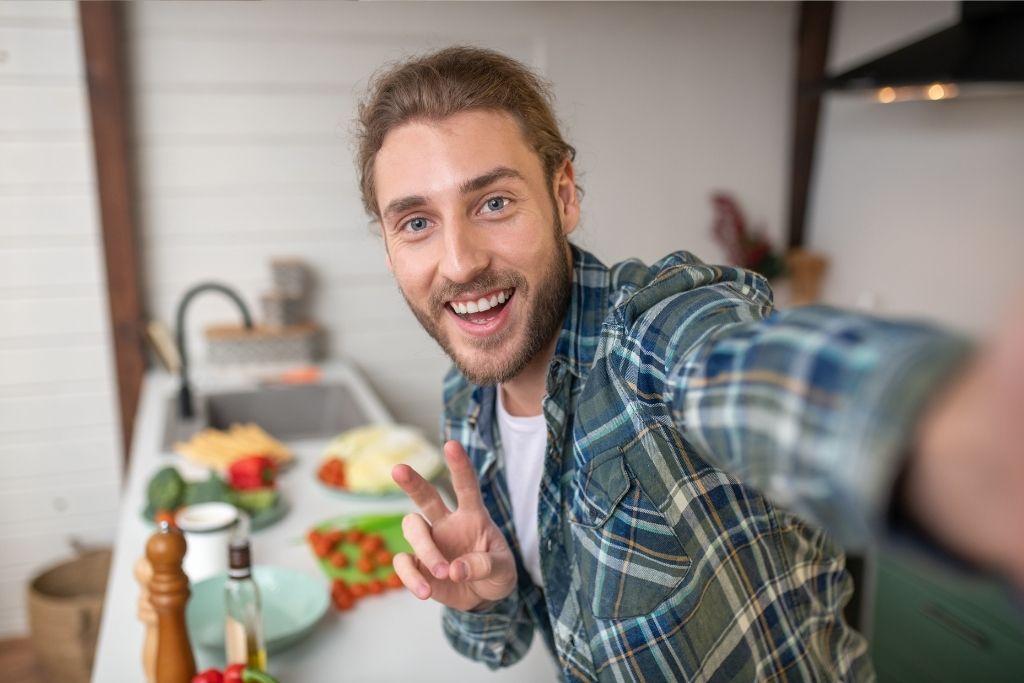 Nuori vegaanimies hymyilee selfiessä