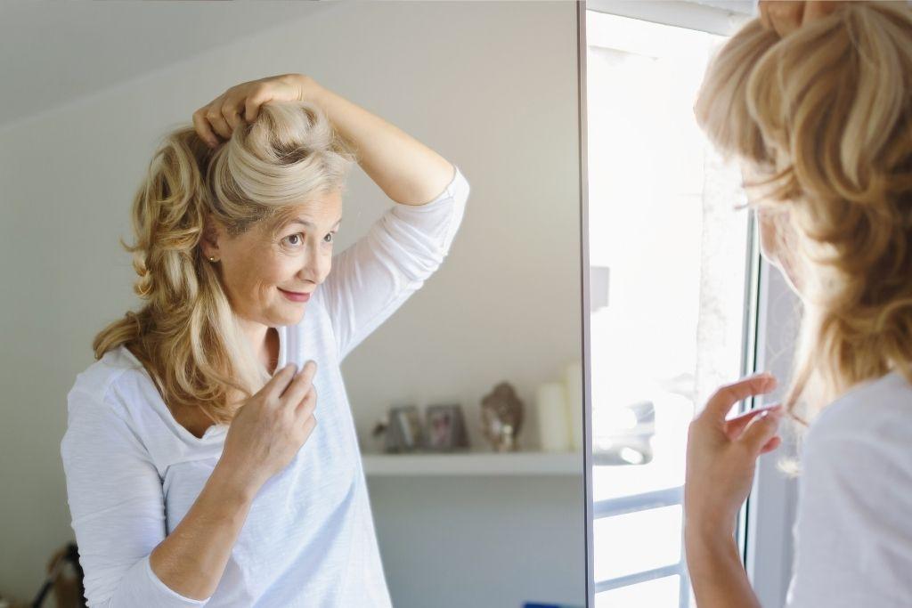 Iäkäs nainen peilaa hiuksiaan.