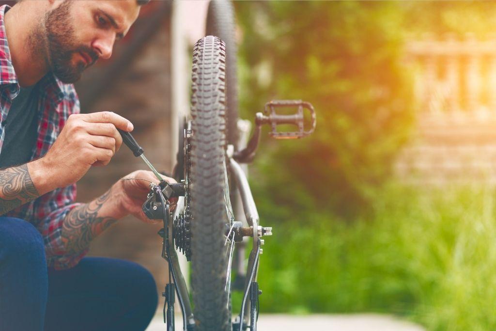 Mies korjaa polkupyöräänsä.