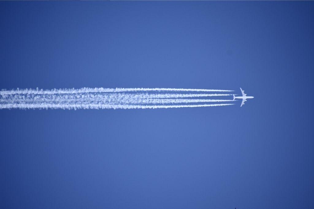 Ilmastonmuutokseen negatiivisesti vaikuttava lentokone taivaalla.