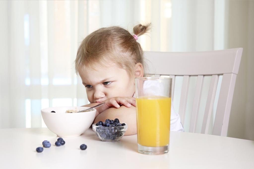 Maitoallerginen lapsi istuu ruokapöydässä eikä halua syödä.