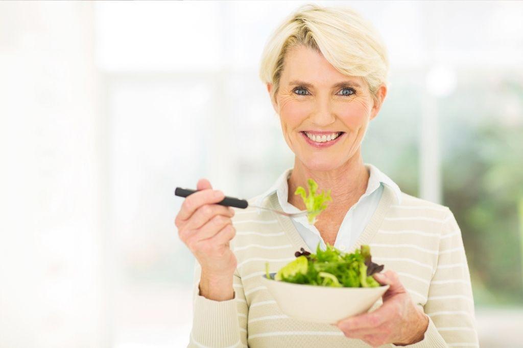 Nainen syö salaattia rauhallisesti.